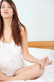 Woman on bed practicing yoga Royalty Free Stock Photo