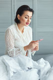 Woman in the bed reading messages. Royalty Free Stock Images