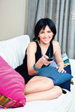 Woman on bed with remote controller. Happy woman on bed with remote controller in hand Royalty Free Stock Images