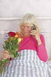 Woman in bed with roses and telephone Stock Photo