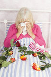 Woman in bed with roses and tissues Stock Photo
