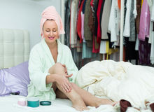 Woman on bed rubbing cream into skin Stock Photography