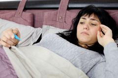 Woman in bed sad about fever Stock Photo