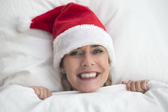 Woman in bed with Santa hat Royalty Free Stock Photography