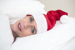 Woman in bed with Santa hat Stock Images