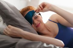 Woman In Bed With Sleep Mask On Eyes Waking Up stock photo
