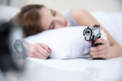 Woman in bed sleeps with hand on gun Stock Photography