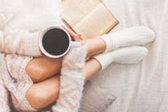 Woman on the bed. Soft photo of woman on the bed with old book and cup of coffee in hands, top view point Royalty Free Stock Photography