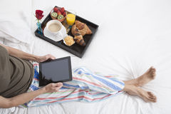 Woman bed tablet breakfast Stock Photography