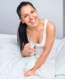Woman at bed taking pills Royalty Free Stock Photos