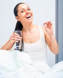 Woman at bed taking pills Stock Photo