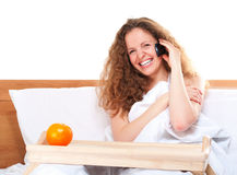 Woman in bed talking by phone Royalty Free Stock Photo
