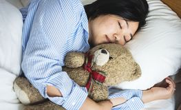 A woman in bed with a teddy bear Royalty Free Stock Images