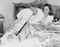 Woman in bed trying to scratch her broken foot with a pole Royalty Free Stock Image