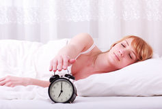 Woman in bed trying to wake up Stock Image