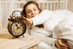Woman in bed turning off alarm clock Royalty Free Stock Image