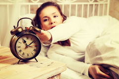 Woman in bed turning off alarm clock Stock Images