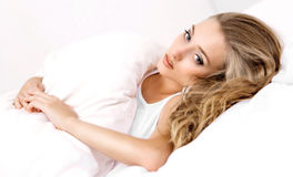 Woman in bed. Unhappy young woman in bed at home Royalty Free Stock Image