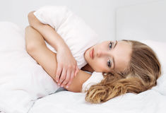 Woman in bed. Unhappy young woman in bed at home Stock Photography