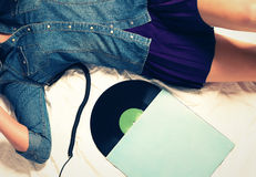 Woman on bed with a vinyl record. Body of woman wearing jeans button down and a skirt on bed with a vinyl record Stock Photography