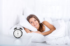 Woman in bed waking up Stock Images