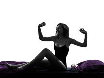 Woman in bed waking up happy stretching silhouette Royalty Free Stock Photos