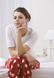 Woman on Bed Wearing Red Polka Dot Pajamas Royalty Free Stock Photography