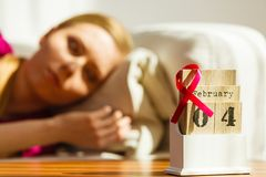 Woman on bed, world breast cancer day on calendar. Woman lying on bed looking at calendar, it is 4 february world breast cancer day, date with pink awareness Royalty Free Stock Images