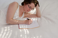 Woman on a bed writing notes stock image