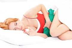 Woman in bed. Young woman in bed, with hot water bag on her tummy royalty free stock image