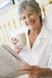 Woman in bedroom with coffee and newspaper smiling Royalty Free Stock Images