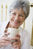Woman in bedroom with coffee smiling Royalty Free Stock Image