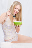 Woman in bedroom holding spoon and plate Stock Photography
