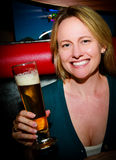 Woman with Beer. A sexy woman smiling holding a beer Royalty Free Stock Photo