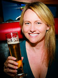 Woman with Beer. A sexy woman smiling holding a beer Royalty Free Stock Image