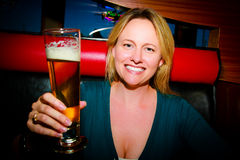 Woman with Beer. A sexy woman smiling holding a beer making a toast Stock Photography