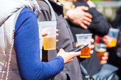 Woman with a beer holding a phone Stock Image