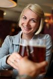 Woman with beer in a pub. Young woman with beer toasting in a pub royalty free stock photography