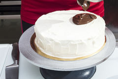 The woman begins to pour cake by melted chocolate Stock Images