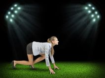 Woman begins to start. Green grass and black sky Stock Image