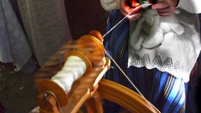 The woman behind an ancient distaff spins white woolen thread stock video