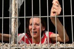 Woman behind bars crying stock photos