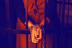 Woman behind bars. Female crime concept. Girl`s hands tied with chains, domestic violence