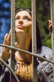 Woman behind bars at night Stock Photo