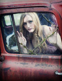 Woman behind broken window. A pale young woman looking through a broken window of an old truck royalty free stock photo