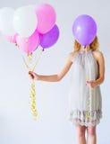 Woman behind bunch of balloons Stock Photos