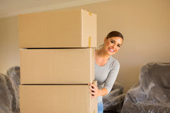 Woman behind cardboard boxes. Excited woman standing behind cardboard boxes in new home Royalty Free Stock Images