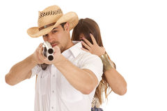 Woman behind cowboy with gun aming close Stock Photography