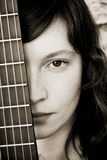 Woman behind guitar fretboard. Woman behind fretboard in sepia stock photos