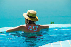 Woman from behind in hat and infinity pool looking away. New travel season concept. 2017 written on back by suncream Royalty Free Stock Photography